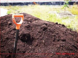 Куча плодородного грунта с воткнутой лопатой