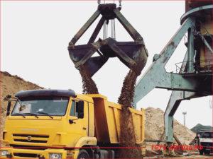 КАМАЗ желтого цвета на погрузке речного песка в карьере