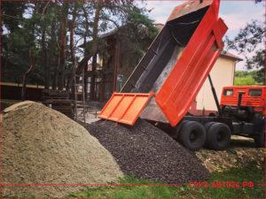 КАМАЗ разгружает гравий и песок на строительстве частного дома
