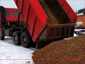 КАМАЗ разгружает желтый щебень для строительства дороги