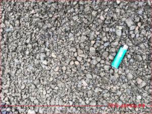 Зажигалка лежит на песчано-щебеночной смеси
