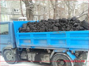 Синий грузовик в кузове уголь для отопления