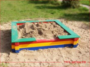 Детская песочница во дворе дома с новым песком
