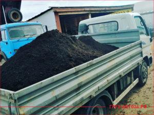 Маленький грузовик в кузове с черноземом