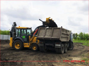 Трактор загружает новый чернозем в кузов КАМАЗа