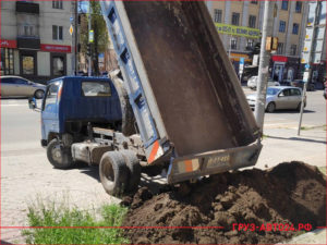 Маленький синий грузовик высыпает чернозем на клумбу возле магазина