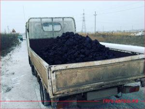 Белый японский грузовик в кузове уголь