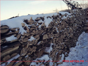 Большая стопка горбыля на складе компании под снегом