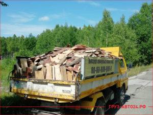 Желтый грузовик везет горбыль по лесной дороге в деревню