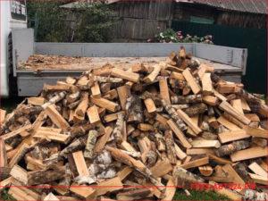 Разгрузка колотых березовых дров во дворе дома