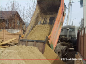 КАМАЗ разгружает песок во дворе дома